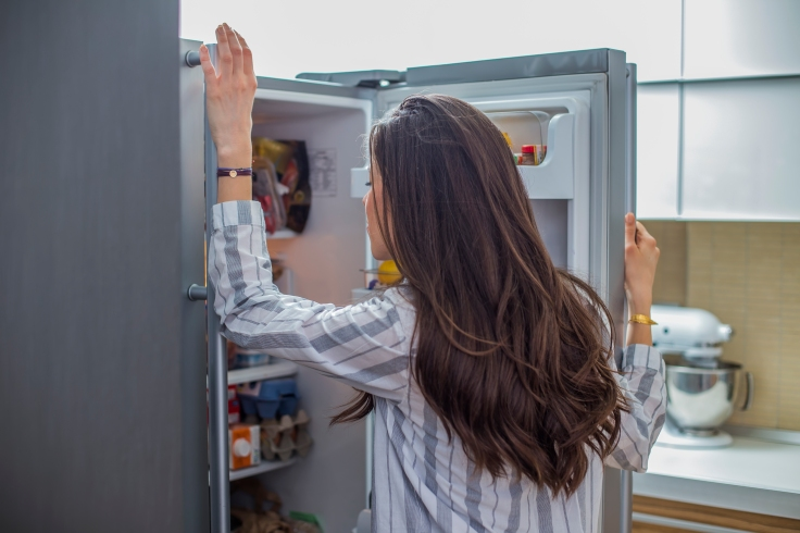 Woman in the kitchen in front of the refrigerator